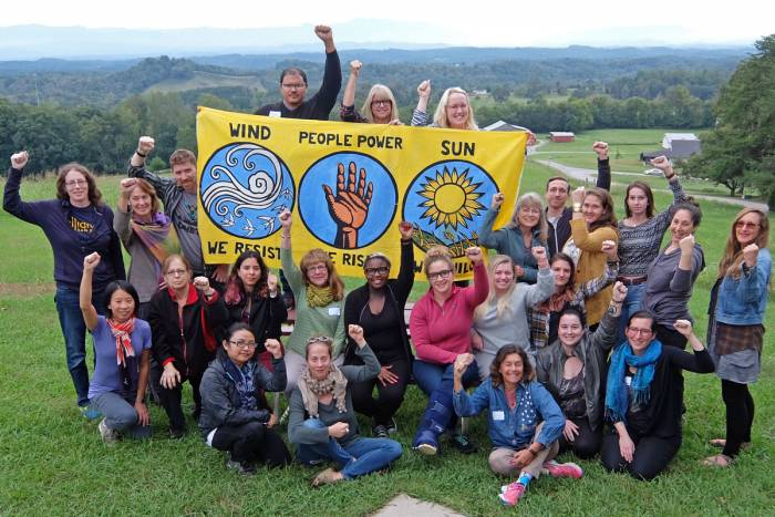 Group on a grassy hill with fists in the air holding a banner that represents the power of wind, sun, and people rising together